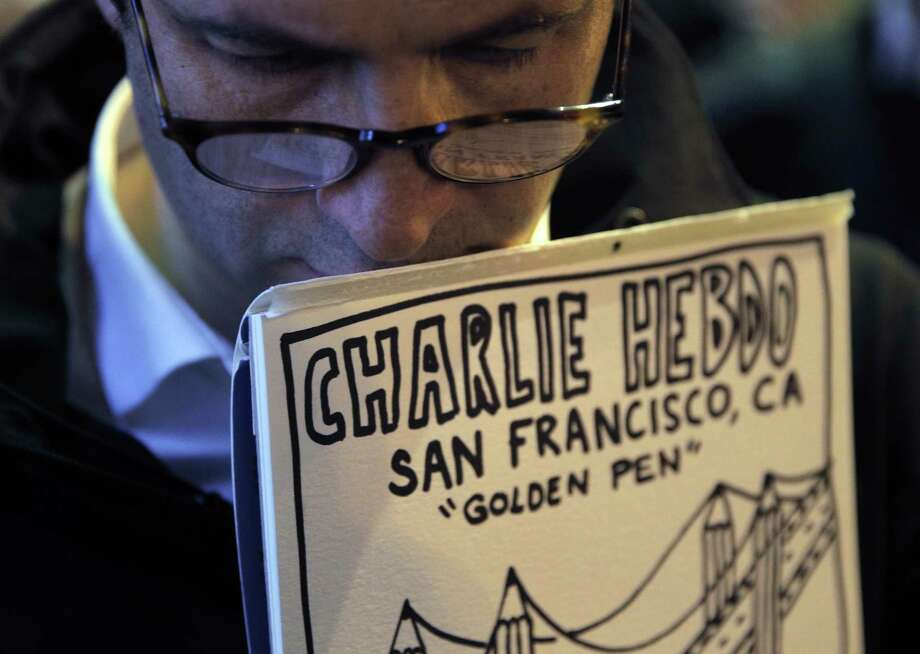 Regis Danon of Santa Clara holds a drawing honoring newspaper Charlie Hebdo during a vigil on the sidewalk outside the French Consulate General in San Francisco, Calif., on Wednesday, January 7, 2015. The vigil honored 12 journalists and cartoonists at the offices of Charlie Hebdo who were killed in Paris earlier in the day. Photo: Carlos Avila Gonzalez / The Chronicle / ONLINE_YES
