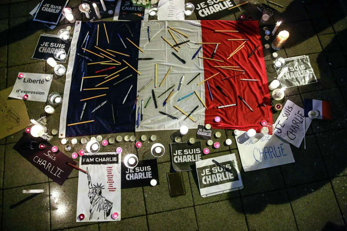 Pens and pencils are placed on the French flag during a vigil in Seattle after a shooting at the French satirical publication Charlie Hebdo left 12 people dead. Gunmen stormed into the Paris office, killing employees of the publication that were gathered for a meeting. Islamic extremists claimed responsibility for the attack. Photographed on Wednesday, January 7, 2014.