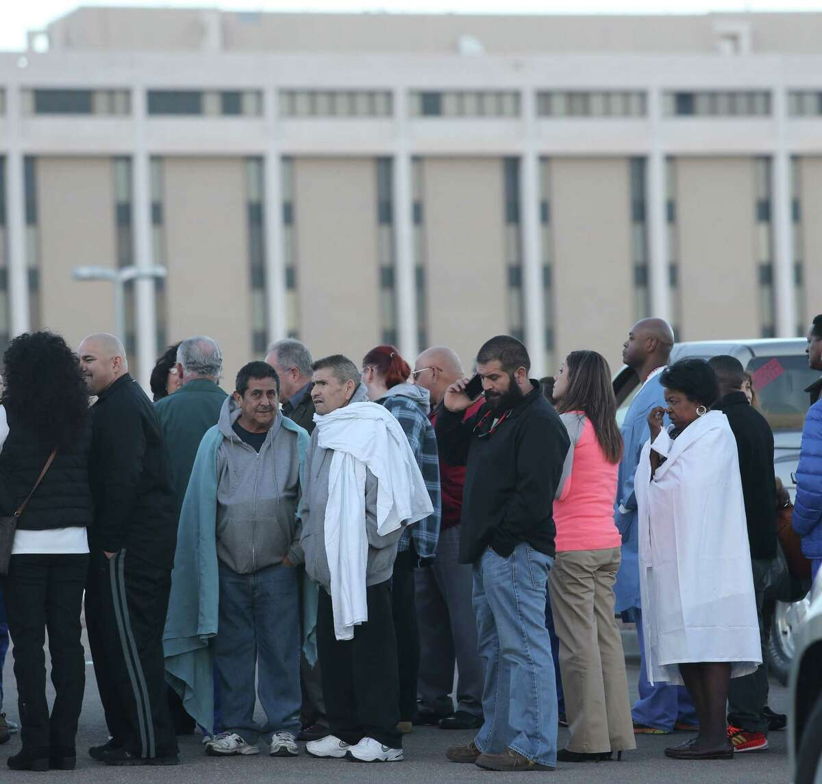 People were gathered in a parking lot outside the El Paso VA following a shooting inside the faciity Tuesday, Jan. 6, 2015. A gunman opened fire at a veterans' medical clinic in West Texas on Tuesday, killing one other person, officials said. The gunman was also killed. (AP Photo/The El Paso Times, Victor Calzada)