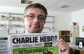 Stephane Charbonnier, known as Charb, publishing director of the satiric weekly Charlie Hebdo, holds up the paper's front page in 2012.