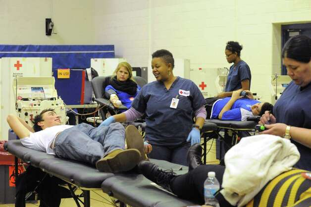 Albany High School senior Liam Hill, left, gives blood with the assistance of phlebotomist Ebony Edwards during a blood drive at Albany High School on Thursday Jan. 8, 2015 in Albany, N.Y. (Michael P. Farrell/Times Union) Photo: Michael P. Farrell / 00030099A