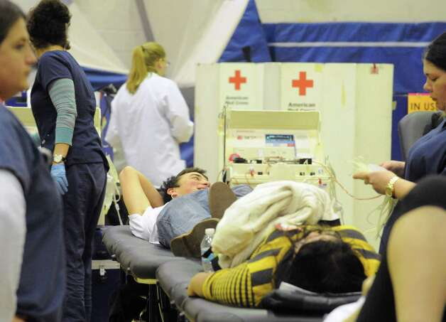 Albany High School senior Liam Hill, center, gives blood during a blood drive at Albany High School on Thursday Jan. 8, 2015 in Albany, N.Y. (Michael P. Farrell/Times Union) Photo: Michael P. Farrell / 00030099A