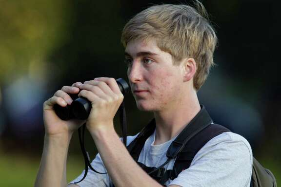 Bird enthusiast Logan Kahle, 17, looks for a rustic bunting at Golden Gate Park in San Francisco, Calif. on Tuesday, Jan 6, 2015. Birdwatchers are flocking to the park to catch a glimpse of the rare species.