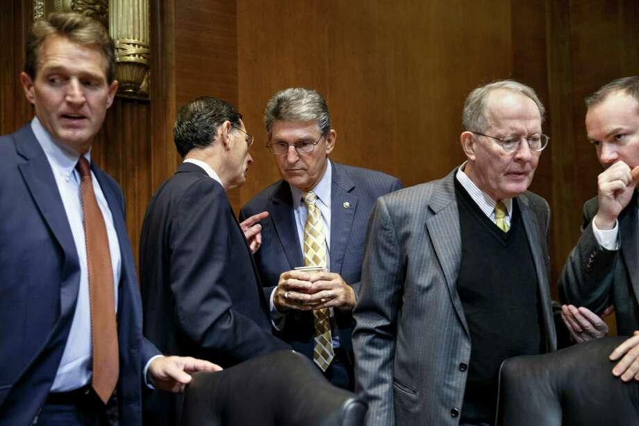 Sen. Joe Manchin, D-W.Va., confers with Republican colleagues about the Keystone XL pipeline. Photo: J. Scott Applewhite / Associated Press / AP