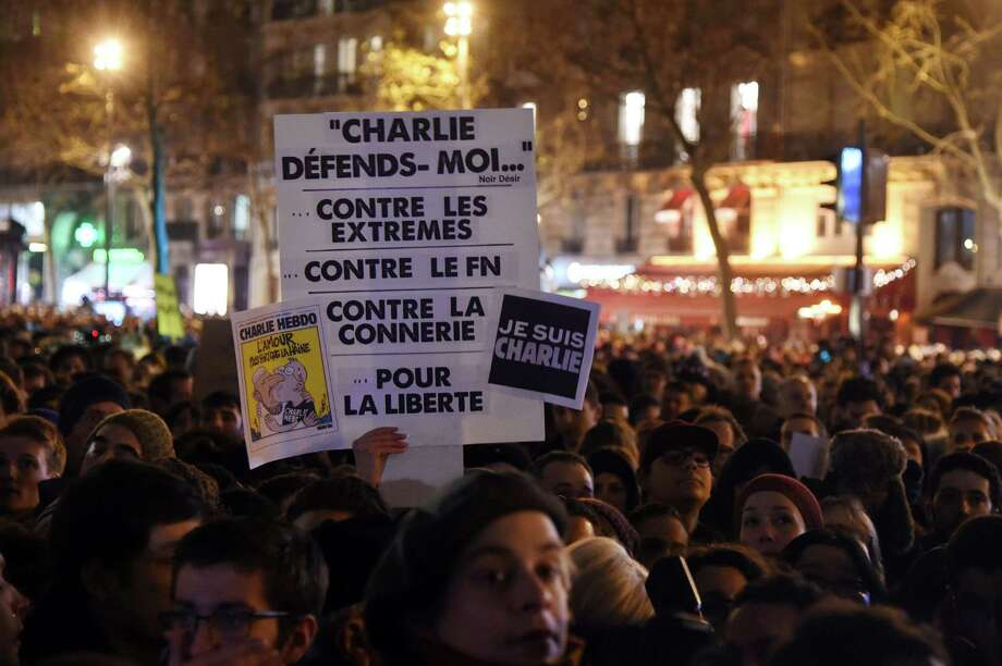 "A person holds placards reading ""Charlie, Defend me .. against the extremes, against the FN (French far-right political party Front National), against bullshit, for liberty"" (C) ; ""Love is stronger than hate"" and ""I am Charlie"", during a gathering at the Place de la Republique (Republic square) in Paris, on January 7, 2015, following an attack by unknown gunmen on the offices of the satirical weekly, Charlie Hebdo. France's Muslim leadership sharply condemned the shooting at the Paris satirical weekly that left at least 12 people dead as a ""barbaric"" attack and an assault on press freedom and democracy. AFP PHOTO / DOMINIQUE FAGETDOMINIQUE FAGET/AFP/Getty Images Photo: DOMINIQUE FAGET / AFP/Getty Images / AFP"