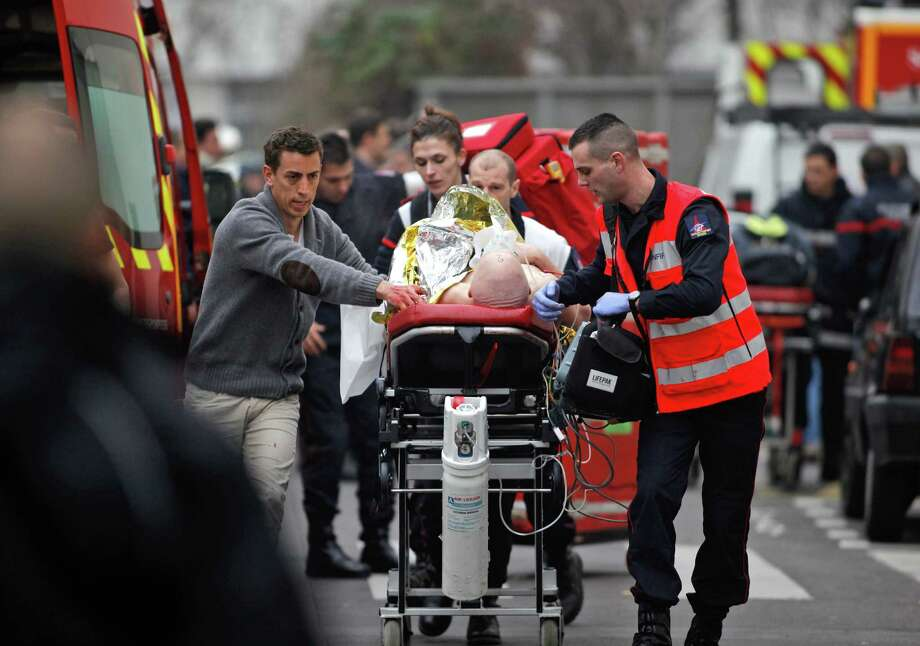 An injured person is transported to an ambulance after a shooting, at the French satirical newspaper Charlie Hebdo's office, in Paris, on Wednesday. Photo: Thibault Camus / Associated Press / AP