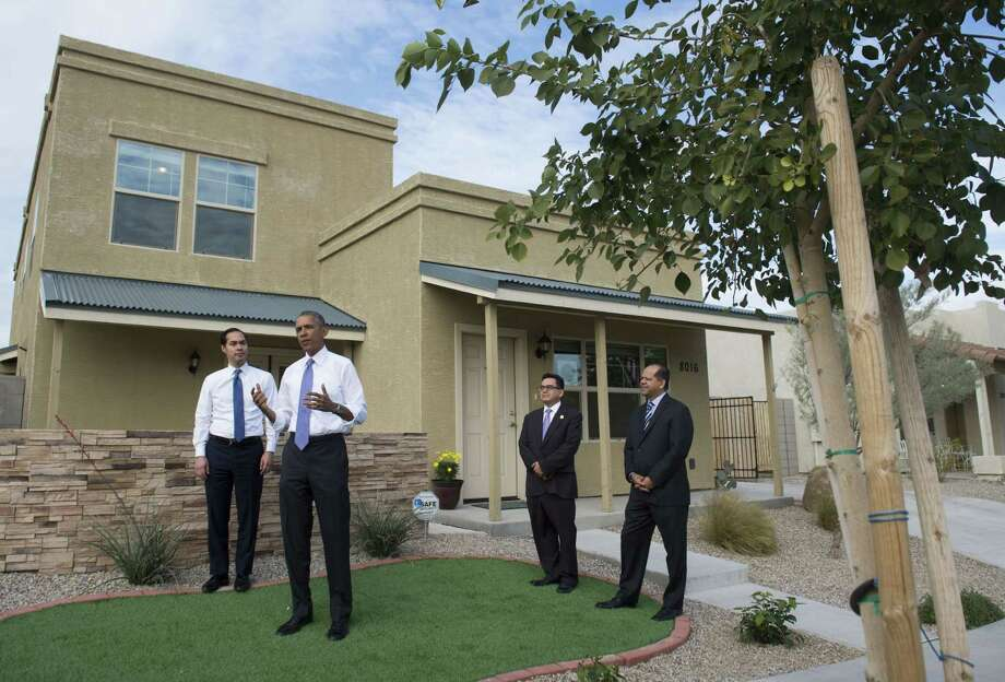 President Obama speaks about his plan to lower some mortgage insurance premiums in a Phoenix neighborhood, while Housing and Urban Development Secretary Julian Castro (left) and Edmundo Hidalgo and David Adame of Chicanos Por La Causa listen. Photo: SAUL LOEB / AFP/Getty Images / AFP