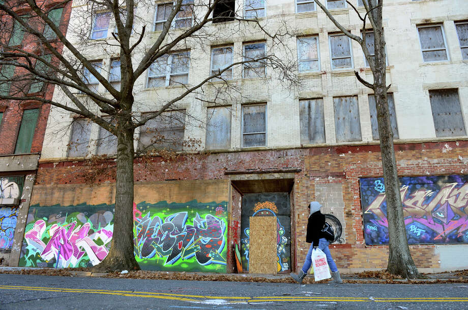 A woman makes her way past a block of closed buildings which are part of downtown north in Bridgeport, Conn. on Thursday Jan. 8, 2015. Mayor Bill Finch announced a city plan to develop these buildings and make them into apartments and businesses. Photo: Christian Abraham / Connecticut Post