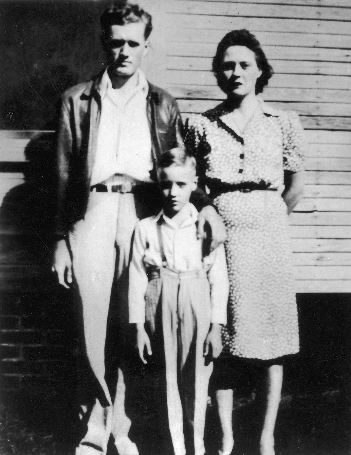 Elvis Presley standing between his parents outside of their home in Tupelo.
