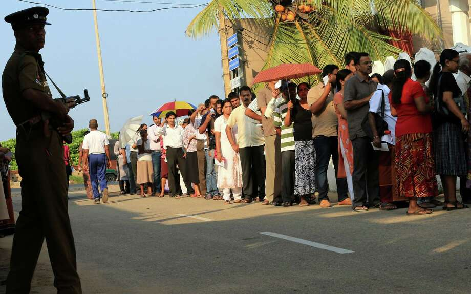Sri Lankans wait in line to vote as a police officer stands guard at a polling station in Colombo. Photo: Buddhika Weerasinghe / Getty Images / 2015 Getty Images