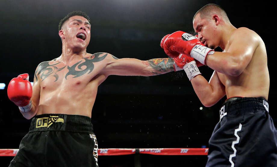 Ivan Najera (left) hits Angel Hernandez during their lightweight bout on March 1, 2014 at the Alamodome. Najera won by a unanimous decision. Photo: Edward A. Ornelas /San Antonio Express-News / © 2014 San Antonio Express-News