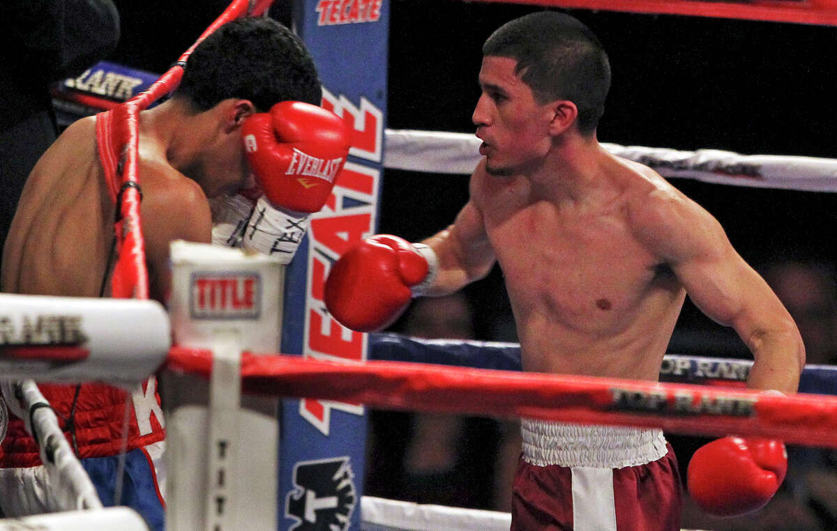 Adam Lopez punches his opponent Ramon Bayala into the ropes during their fight at the Alamodome on March 31, 2012.