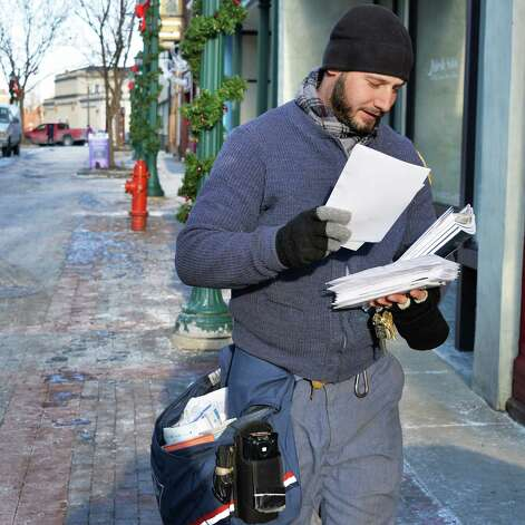 """Postal carrier Andrew Mokey of Watervliet delivers mail along Jay Street Thursday Jan. 8, 2015, in Schenectady, NY. """"It is cold, but that's what we do, just layer up and take it one letter at a time.""""   (John Carl D'Annibale / Times Union) Photo: John Carl D'Annibale / 00030121A"""