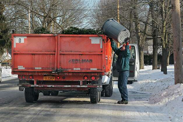 City workers pick up discarded Christmas trees and other debris from trees from the side of the road on Thursday, Jan. 8, 2015 in Saratoga Springs, N.Y.  (Lori Van Buren / Times Union) Photo: Lori Van Buren / 00030121A