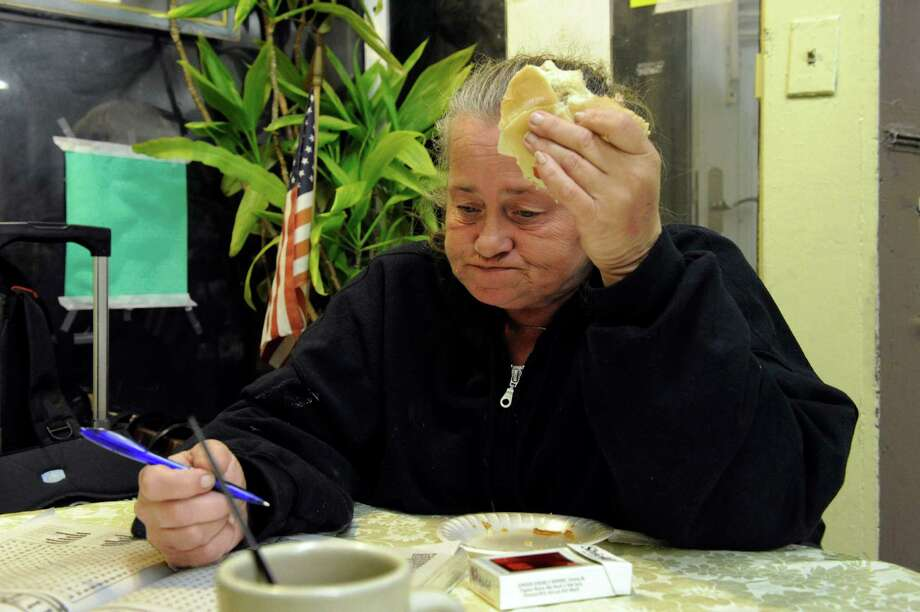 Sandra Veness, 53, eats a sandwich while playing a word search game Friday night at the Dorothy Day Hospitality House on Spring Street in Danbury, Conn. Veness is taking advantage of the Shelter from the Cold program offered by Dorothy Day during the winter months. Photo: Carol Kaliff / The News-Times