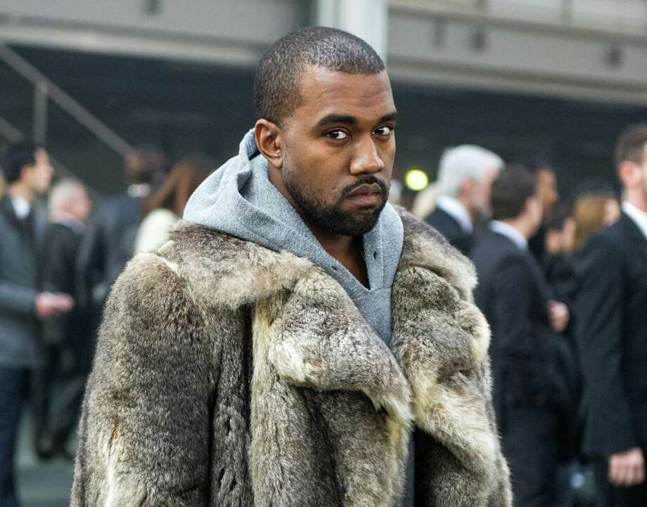 FILE - This Jan. 17, 2014 file photo shows singer Kanye West as he arrives for the Givenchy men's Fall-Winter 2014-2015 fashion collection in Paris.  West will not face criminal charges over an incident in which he apparently punched a man in a Beverly Hills chiropractor's office, prosecutors determined Friday, Jan. 31. The Los Angeles County District Attorney's Office rejected a battery case against the rapper because he had reached a civil settlement with the man and there were no significant injuries documented after the altercation. The altercation occurred after the 18-year-old man used a racial slur in an argument with West's fiancee, Kim Kardashian, on Jan. 13, according to a document prepared by a prosecutor.  (AP Photo/Zacharie Scheurer, File) ORG XMIT: NYET631 Photo: Zacharie Scheurer / AP