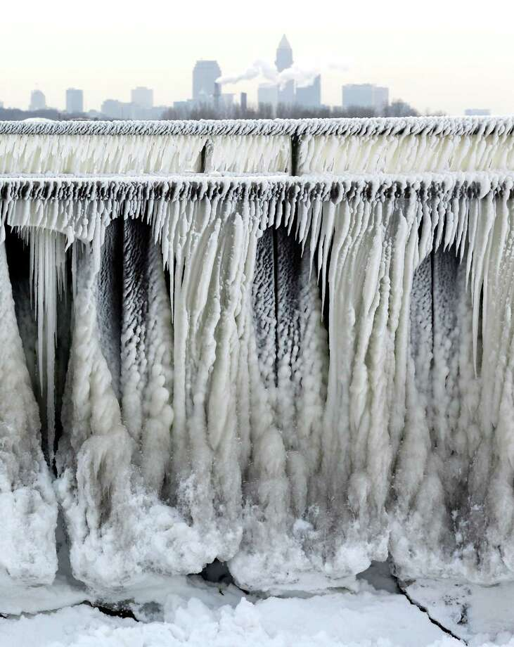 Ice from Lake Erie forms on a pedestrian walkway as the city of Cleveland is seen in the background. Photo: Tony Dejak / Associated Press / AP
