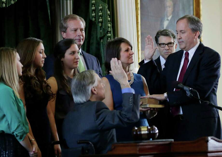Ken Paxton, right, is sworn in as Texas attorney general by Gov.-elect Greg Abbott, center, Paxton is joined by his family and Gov. Rick Perry, second from right. A reader says Paxton's legal issues will damage his credibility as a public official. Photo: Eric Gay /Associated Press / AP