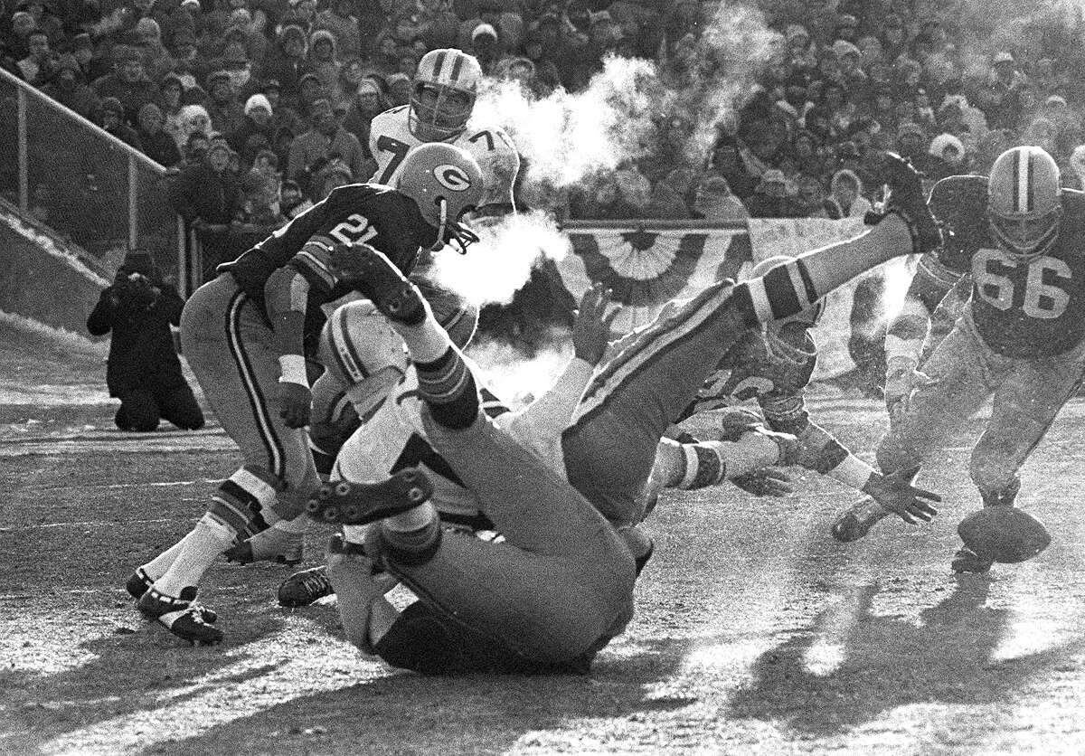 Dallas Cowboys quarterback Don Meredith (17) falls backward onto a Green Bay Packers player as he fumbles tha ball in the third quarter of the NFL championship game, known as
