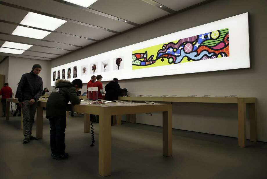 Artwork from artists Roz Hall, left, Christian Weber, center, and Craig Redman and Karl Maier is on display on the wall of an Apple Store in New York, Thursday, Jan. 8, 2015. Apple is turning its retail stores into art galleries featuring the work of professional photographers and other artists who use iPads, iPhones and Mac computers to create. (AP Photo/Seth Wenig) Photo: Seth Wenig / Associated Press / AP