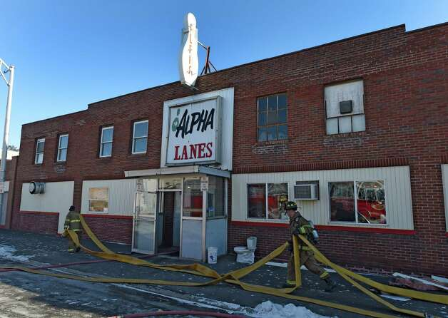 Firefighters clear hose lines used to knockdown a small but stubborn fire in the walls of the Alpha Bowling Lanes Thursday afternoon Jan. 8, 2015 in Troy, N.Y.  (Skip Dickstein/Times Union) Photo: SKIP DICKSTEIN