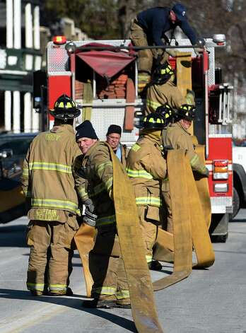 Firefighters clear water hoses used to knockdown a small but stubborn fire in the walls of the Alpha Bowling Lanes Thursday afternoon Jan. 8, 2015 in Troy, N.Y.  (Skip Dickstein/Times Union) Photo: SKIP DICKSTEIN