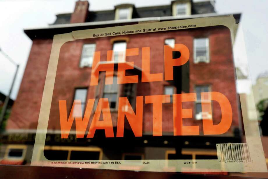 A Philadelphia business displays a help wanted sign in its storefront. With the price of oil below $50 a barrel, consumers will have steadily more money to spend, potentially creating job openings at retailers, auto dealers, restaurants and hotels. Photo: Associated Press File Photo / AP