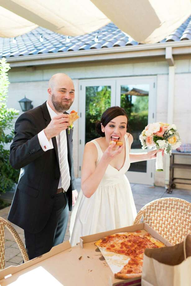 Greg Tucker and Jenna Beck (she'd been too nervous to eat earlier in the day) share a quick bite of pizza that the groomsmen had ordered earlier before the wedding gets under way. Photo: Caitlin O'Reilly / Caitlin O'Reilly Photography / ONLINE_YES