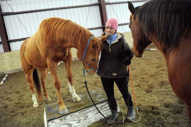 Horsewoman Valerie Buck works with Budder, left, and Whiskey on Wednesday, Jan. 7, 2015, at Long Shadows Farm in Cambridge, N.Y. Buck, formerly with Saratoga War Horse, has started a new equine therapy program for women who have experienced trauma called ACTT Naturally. (Cindy Schultz / Times Union) Photo: Cindy Schultz / 00030061A