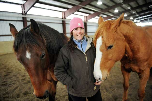 Horsewoman Valerie Buck with Whiskey, left, and Budder on Wednesday, Jan. 7, 2015, at Long Shadows Farm in Cambridge, N.Y. Buck, formerly with Saratoga War Horse, has started a new equine therapy program for women who have experienced trauma called ACTT Naturally. (Cindy Schultz / Times Union) Photo: Cindy Schultz / 00030061A
