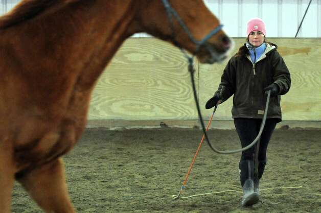 Valerie Buck uses natural horsemanship techniques to work with Budder on Wednesday, Jan. 7, 2015, at Long Shadows Farm in Cambridge, N.Y. Buck, formerly with Saratoga War Horse, has started a new equine therapy program for women who have experienced trauma called ACTT Naturally. (Cindy Schultz / Times Union) Photo: Cindy Schultz / 00030061A