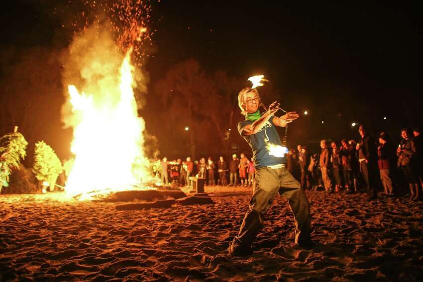 Kingsley Casayuran dances with fire as Christmas trees are tossed into a bonfire at Golden Gardens Beach Park. Nearly 100 Christmas trees were set ablaze in a fire pit during the annual Point83 cyclist club tree burn.