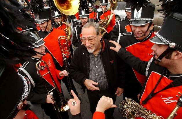 """Band director David Bournazian, center, listens while members of the Mohonasen High Marching Band talk him into changing the first song to Buddy Rich's """"Channel One Suite"""" before the start of the Veterans' Day Parade on Thursday, Nov. 11, 2004, in Albany, N.Y. (Cindy Schultz / Times Union)"""