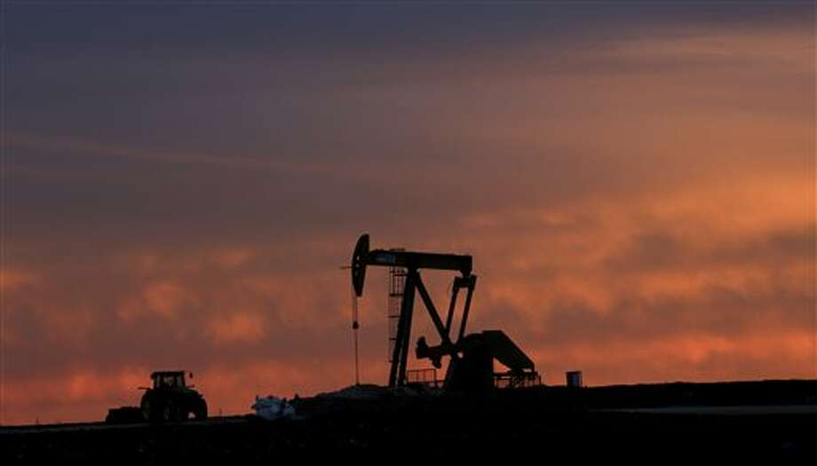 In this photo made Monday, Dec. 22, 2014, a well pump works at sunset on a farm near Sweetwater, Texas. At the heart of the Cline, a shale formation once thought to hold more oil than Saudi Arabia, Sweetwater is bracing for layoffs and budget cuts, anxious as oil prices fall and its largest investors pull back. (AP Photo/LM Otero) Photo: LM Otero, AP / AP