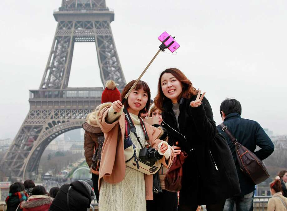 Tourists in Paris use a selfie stick to capture a photo with the Eiffel Tower in the background.Take a look at our gallery to see which Texas museums are banning the device. Photo: Remy De La Mauviniere, STF / AP