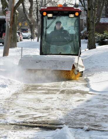 Tim Reilly of the College of Saint Rose maintenance department clears fresh snow from sidewalks along Western Avenue Friday morning, Jan. 9, 2015, in Albany, N.Y.  (John Carl D'Annibale / Times Union) Photo: John Carl D'Annibale / 00030144A