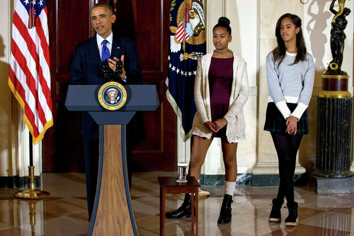 FILE - In this Nov. 26, 2014 file photo, President Barack Obama, joined by his daughters Malia, right, and Sasha, center, speaks at the White House, in Washington during the presidential turkey pardon ceremony, an annual Thanksgiving tradition. An aide to a Republican congressman has resigned after her critical comments about President Barack Obama's daughters touched off a backlash. Elizabeth Lauten, communications director to Rep. Stephen Fincher of Tennessee, commented on Malia and Sasha Obama's pose and dress at a White House ceremony last week in which the president pardoned a turkey. She wrote that the girls should have shown more class. Lauten later apologized for the comments on her Facebook page that had drawn harsh criticism.(AP Photo/Jacquelyn Martin, File)