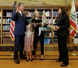 Lt. Gov. Gavin Newsom (left) takes the oath of office from Attorney General Kamala Harris (right) alongside his family in Sacramento on Jan. 5. Newsom was accompanied by his wife, Jennifer, and daughters Montana (second from left) and Brooklynn.