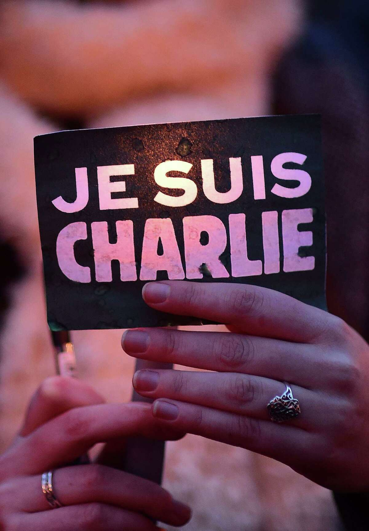"""A woman holds a sign reading """"Je suis Charlie"""" (I am Charlie) during a gathering in Brussels on January 9, 2015 to pay tribute to the victims of a deadly attack on the Paris headquarters of French weekly Charlie Hebdo. Elite commandos units killed the two suspects in the Charlie Hebdo massacre during a simultaneous assault on the building they were holed up in and on a Paris Jewish supermarket, freeing hostages at both sites. AFP PHOTO / EMMANUEL DUNANDEMMANUEL DUNAND/AFP/Getty Images"""