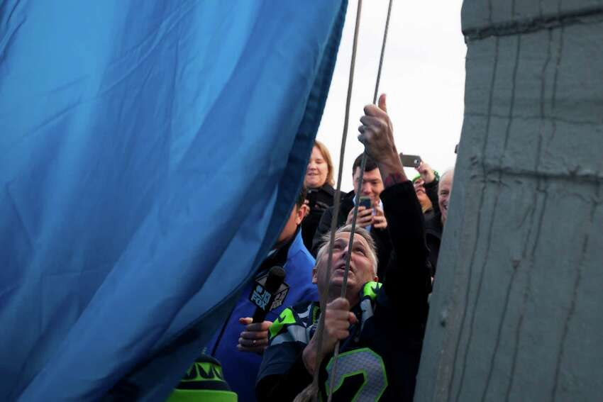 In celebration of the Seahawks playoff game, Pearl Jam lead guitarist, Mike McCready, raises the 12th man flag on the roof of the Space Needle at 9 a.m. on Friday, January 9, 2015.