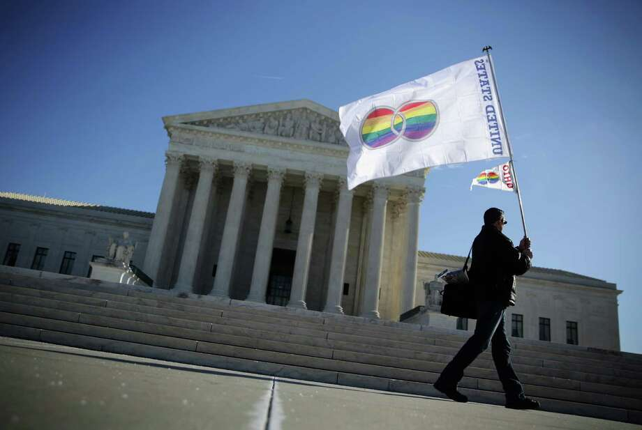 "Pete Prete of Equality Beyond Gender holds a ""marriage pride flag"" outside the U.S. Supreme Court January 9, 2015 in Washington, DC. The justices of the Supreme Court were scheduled to meet to determine whether the court will take up any of the five pending state-banned same-sex marriage cases in Ohio, Tennessee, Michigan, Kentucky and Louisiana. Photo: Alex Wong / Getty Images / 2015 Getty Images"