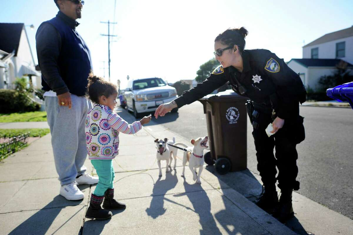 Right: Richmond Officer Cortez gives Mylie Janison, 2, a sticker on her dog walk with dad Michael Janison.