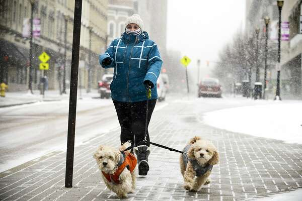 Laura Towers walkers her dogs along Monroe Center in downtown Grand Rapids on Thursday, Jan. 8, 2015. A winter storm warning with snow and below-freezing windchills is in effect through Friday afternoon. (AP Photo/The Grand Rapids Press, Emily Rose Bennett) ALL LOCAL TELEVISION OUT; LOCAL TELEVISION INTERNET OUT