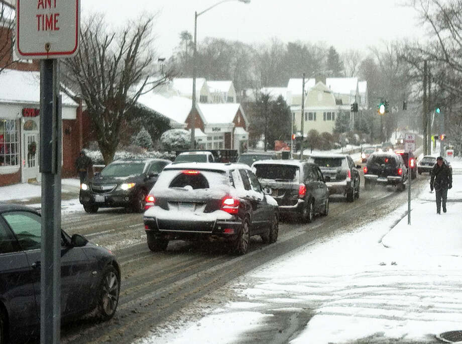 Traffic crawls along slick Park Street during Friday morning's snowfall. Photo: Martin Cassidy / New Canaan News