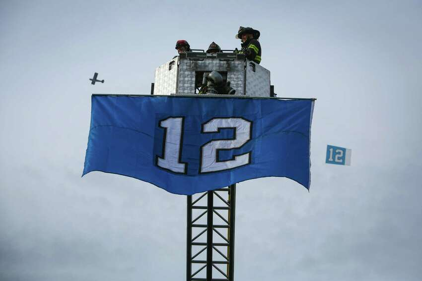 An airplane towing a flag flies behind a flag unfurled from a Renton Fire Department ladder truck during a Seattle Seahawks fan rally at Renton City Hall on Friday, January 9, 2015. Hundreds of Seahawks fans came to the rally to show support for the Hawks before their playoff matchup with the Carolina Panthers.
