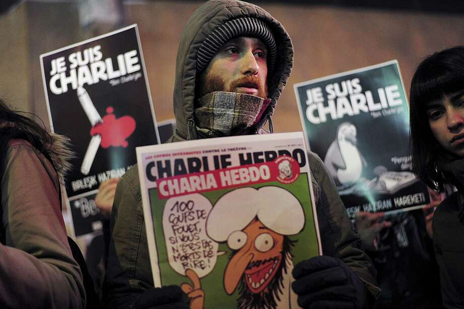 """People hold placards reading """"I am Charlie"""" and frontpage of Charlie Hebdo during a march in Istiklal avenue in Istanbul on January 8, 2015 in tribute to the 12 victims of an attack by armed gunmen on the offices of French satirical newspaper Charlie Hebdo in Paris the day before. Wednesday's massacre triggered poignant and spontaneous demonstrations of solidarity around the world. Photo: OZAN KOSE /AFP /Getty Images / AFP"""