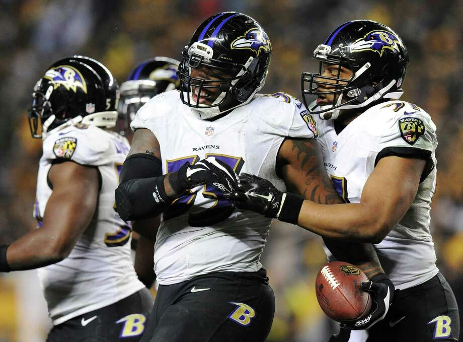 Terrell Suggs (center) celebrates his between-the-legs interception that helped seal a playoff win over Pittsburgh. Photo: Don Wright / Associated Press / FR87040 AP
