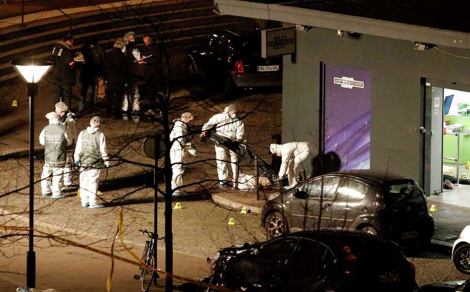 Forensic officers prepare to move a body outside a kosher grocery which was the scene of a hostage taking. A Paris prosecutor said gunman Amedy Coulibaly killed four people when he entered the store. Photo: Francois Mori / Associated Press / AP