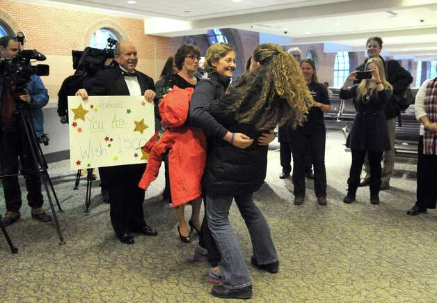 Seventeen-year-old Hannah Priamo, left, of Amsterdam is welcomed back by family and friends from her Make-A-Wish trip to the People's Choice Awards in Los Angeles, and marking the chapter's 1,500th local wish, at Albany International Airport on Friday Jan. 9, 2015 in Colonie, N.Y. (Michael P. Farrell/Times Union) Photo: Michael P. Farrell / 00030131A