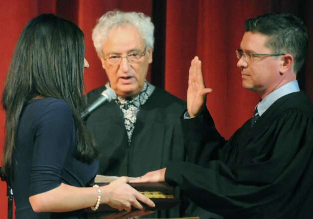Schenectady County Court Judge Matt Sypniewski, right, takes his oath of office from Judge Barry Kramer, center, as his wife Diane holds the bible Friday, Jan. 9, 2015, at Schenectady High School in Schenectady, N.Y. Both Judges Kramer and Sypniewski are graduates of Schenectady High School. (Michael P. Farrell/Times Union) Photo: Michael P. Farrell / 00030123A